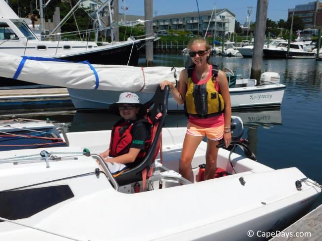 Instructor and sailor on sailboat at dock