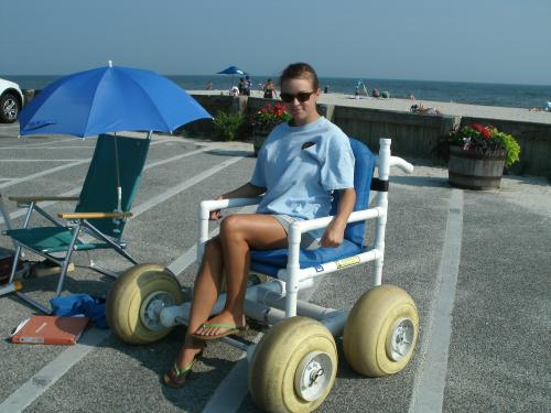 Beach attendant demonstrating an oversand wheelchair