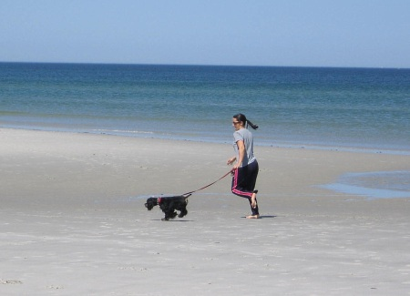 Lady jogging with her dog on a Cape Cod Bay beach